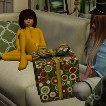 Taelor sitting by Mystina as she opening her present